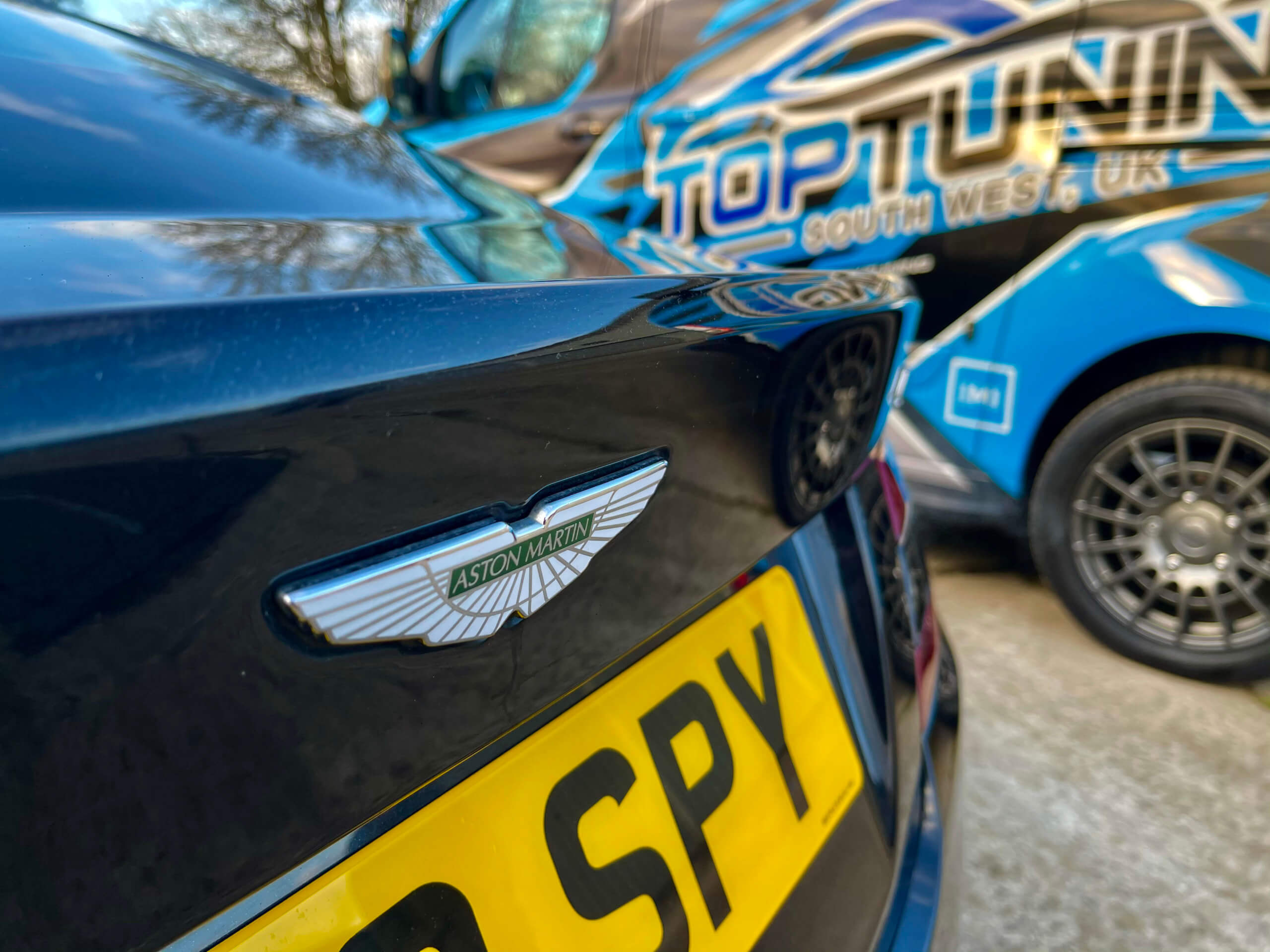 Close up of Aston Martin next to Top-tuning van